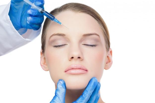 Content aantrekkelijk model met botox injectie op het voorhoofd Premium Foto