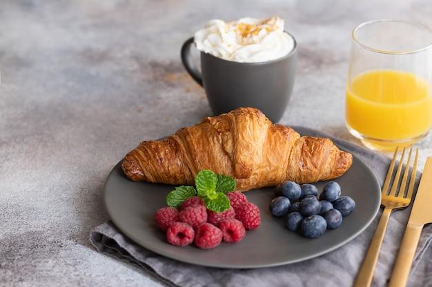 Continentaal ontbijt, franse croissant, koffie met melk, bessen en sinaasappelsap. Premium Foto