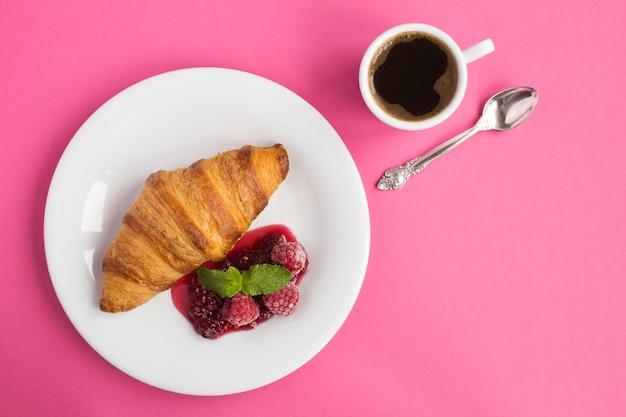Continentaal ontbijt met croissant, koffie en frambozenjam op het roze oppervlak. bovenaanzicht. kopieer ruimte. Premium Foto