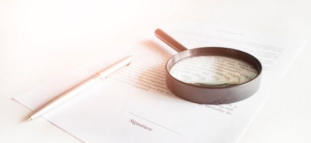 Contract met pen en vergrootglas. bedrijfsconcept Premium Foto