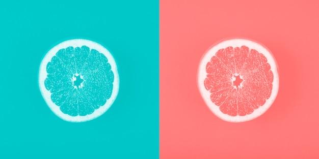 Contrastblauw en koraalachtergrond met grapefruitplak Gratis Foto