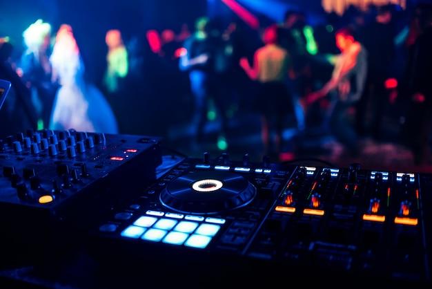 Controle dj voor het mixen van muziek met wazige mensen dansen op feestje in nachtclub Premium Foto
