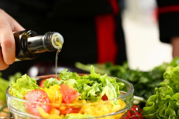Cook houdt fles in de hand en druppelt olijf Premium Foto