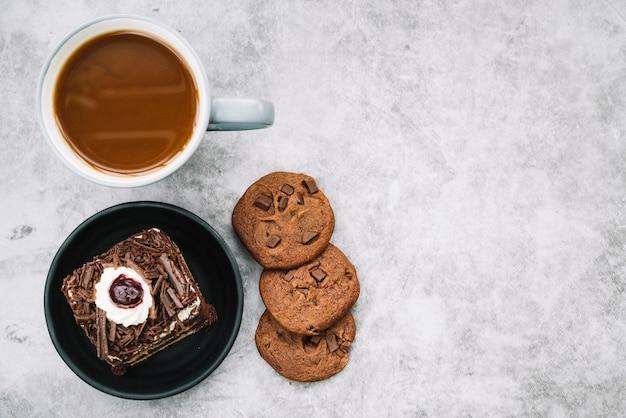 Cookies; koffiekopje en een plakje cake op de achtergrond Gratis Foto
