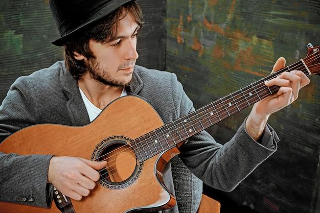 Cool man met hoed gitaarspelen op grijze ruimte Gratis Foto