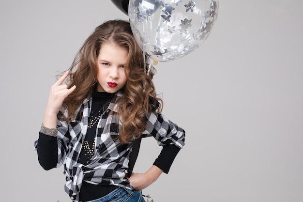 Cool pre-tiener meisje met stenen bord. ze vertoont een rock-'n-roll- of hoornteken, gebaart en pruilt haar lippen met twee luchtballonnen. Premium Foto