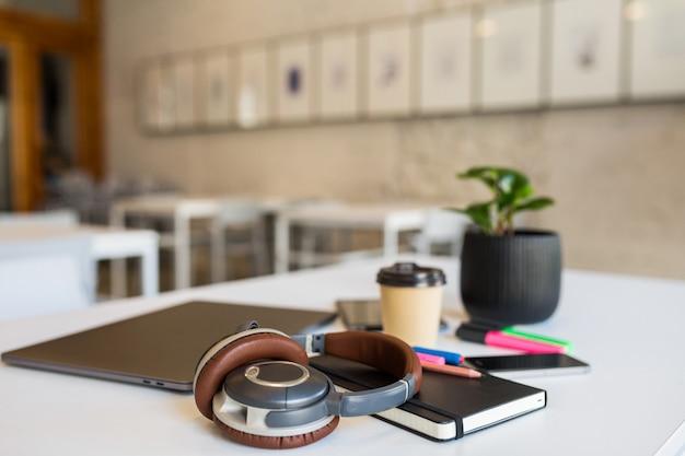 Cool verschillende kantoorbenodigdheden gerangschikt op witte tafel in co-working office Gratis Foto