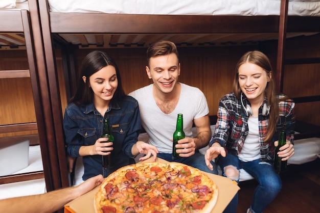 Coole foto van man bracht pizza naar vrienden. Premium Foto