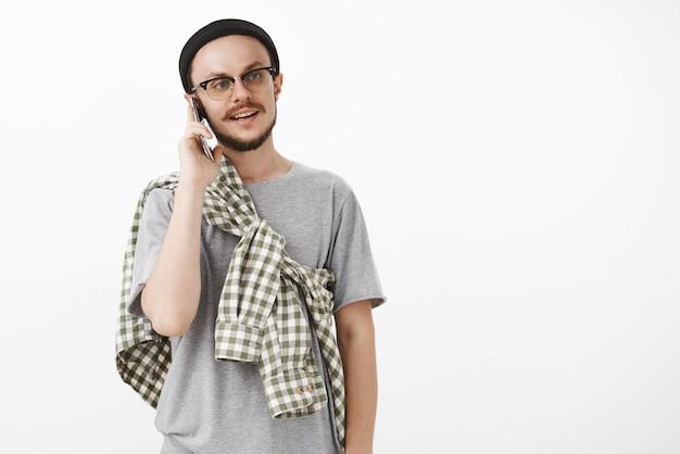 Coole hipster man roept vrienden uitnodigend kom langs en grijp beer met smartphone in de buurt van oor terwijl praten aan de telefoon naar rechts staren met casual normale uitdrukking staande in zwarte muts en bril Gratis Foto
