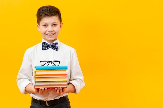 Copy-space jongen die stapel boeken Gratis Foto