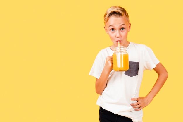 Copy-space jongen fris oranje drinken Gratis Foto
