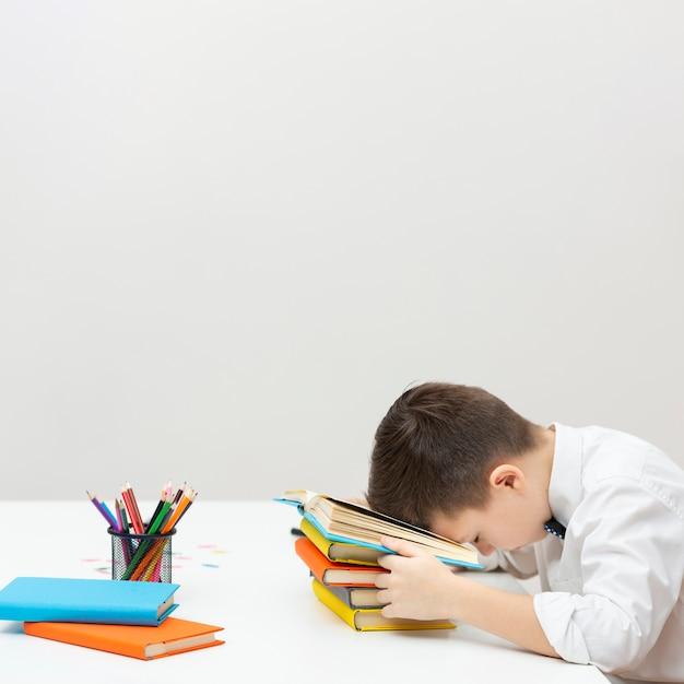 Copy-space jongenszitting met hoofd op boeken Gratis Foto