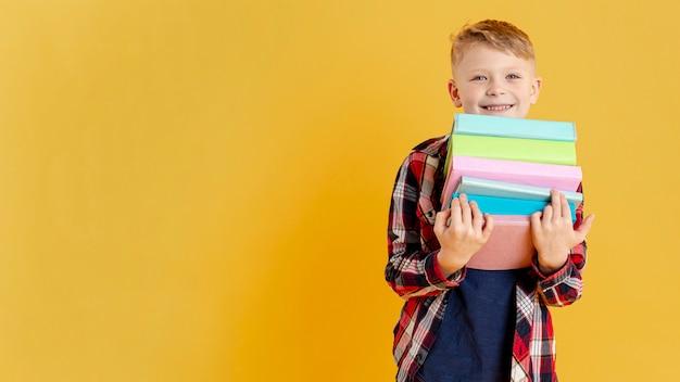 Copy-space kleine jongen met stapel boeken Gratis Foto