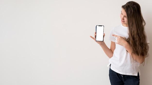Copy-space meisje wijzend op mobiel Gratis Foto