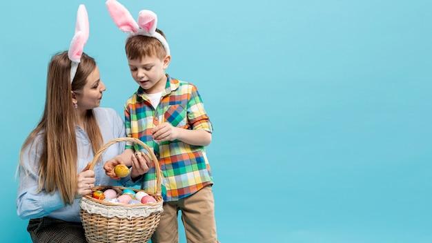 Copy-space moeder en zoon kijken naar mand met eieren Gratis Foto