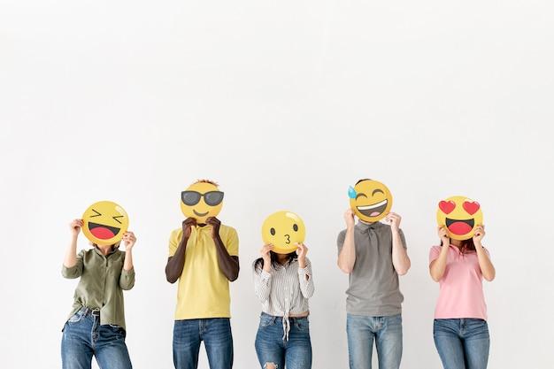 Copy-space vrienden die gezicht bedekken met emoji Gratis Foto