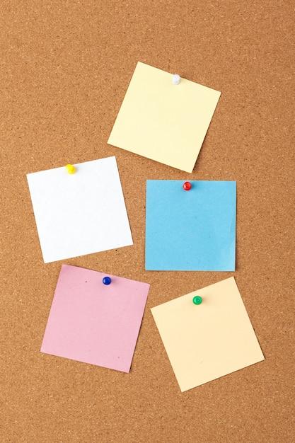 Cork bord met verschillende kleurrijke lege notities met pinnen Premium Foto