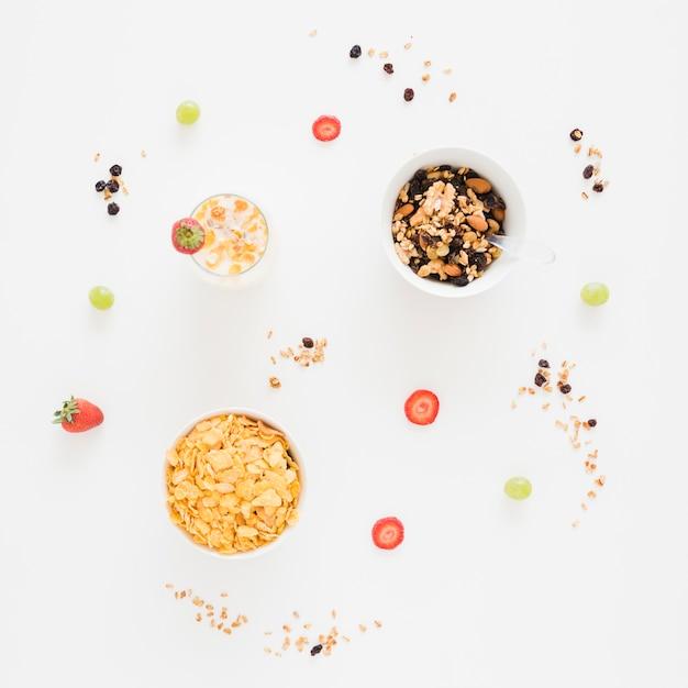 Cornflakes; gedroogde vruchten met aardbei en druiven op witte achtergrond Gratis Foto