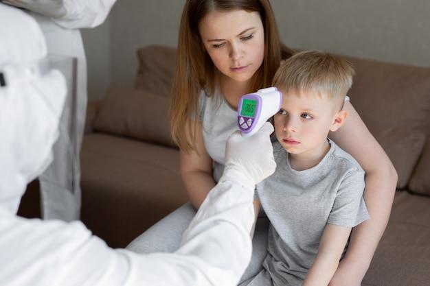 Coronavirus. de arts controleert de lichaamstemperatuur van de jongen met behulp van het infraroodkanon van het voorhoofdthermometer op virus covid-19 symptoom - epidemisch uitbraakconcept. hoge temperatuur. Premium Foto