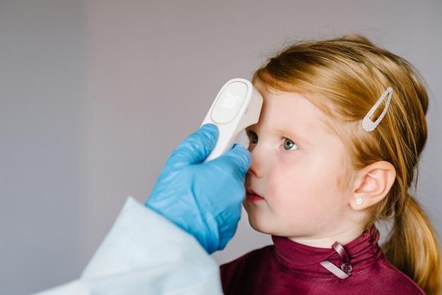 Coronavirus. de verpleegster, arts controleert de lichaamstemperatuur van het meisje gebruikend infrarood voorhoofdthermometer (kanon) voor virussymptoom - concept van de epidemieuitbraak. hoge temperatuur. Premium Foto