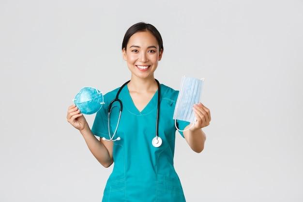 , coronavirus, gezondheidswerkers concept. aangename vrouwelijke arts, aziatische arts in scrubs met gasmasker en medisch masker, biedt personeel persoonlijke beschermingsmiddelen Premium Foto