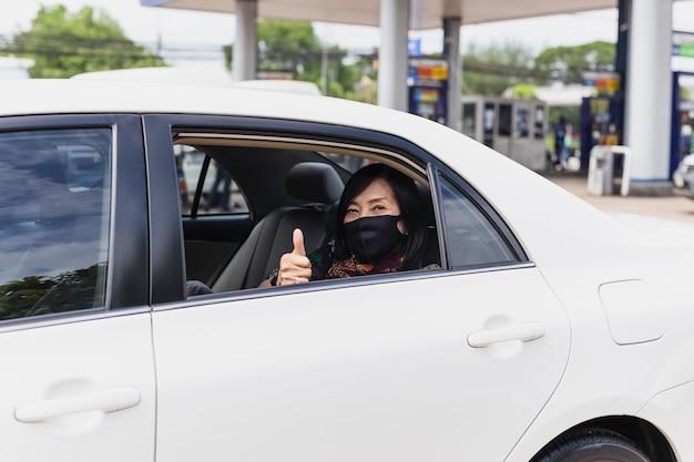 Coronavirus pandemie concept senior vrouw met beschermend masker duim omhoog zitten in een auto road trip reizen. Premium Foto