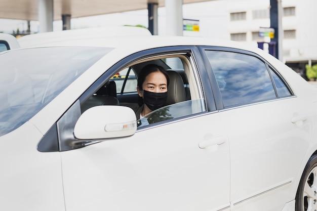 Coronavirus pandemie concept vrouw met beschermend masker zit in een auto road trip reizen. Premium Foto