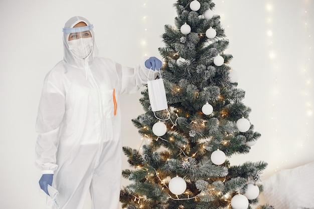 Coronavirus pandemie covid-2019. beschermend pak, bril, handschoenen, masker. kerstboom is versierd met medisch masker. Gratis Foto