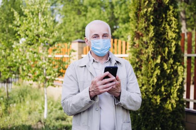 Coronavirus quarantaine, coronavirus, man met medisch gezichtsmasker die de telefoon gebruikt om naar nieuws te zoeken. luchtvervuiling Premium Foto