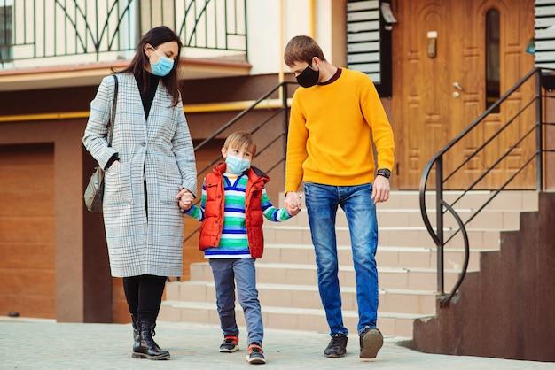 Coronavirus quarantaine. familie gaan wandelen. ouders en kind buiten het dragen van een chirurgisch masker. Premium Foto