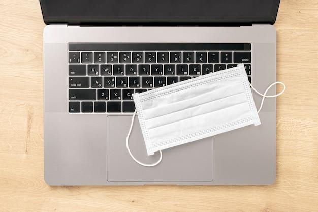 Coronavirus werken vanuit huis concept laptop met beschermend masker op houten tafelblad bekijken Premium Foto