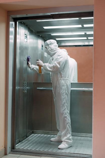 Coronavirusbesmetting. paramedicus in beschermend masker en kostuum die een lift met sproeier desinfecteert, Premium Foto