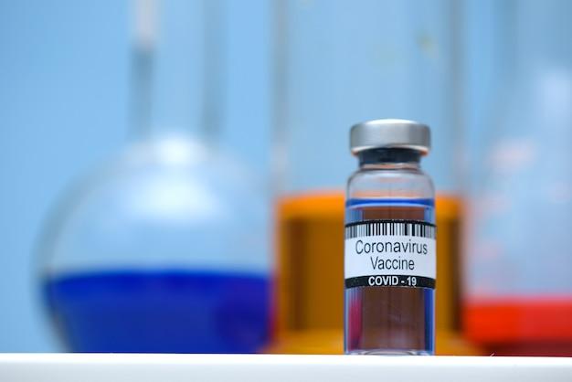 Coronavirusvaccin in fles voor injectie op tafel tegen achtergrond medisch laboratorium Premium Foto