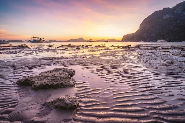 Corong beach, el nido, filippijnen. zonsondergang op tropisch strand. zonreflecties op het gouden uur Premium Foto