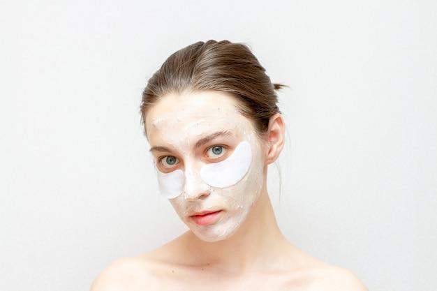 Cosmetisch gezichtsmasker op mooi meisje. jonge vrouw gebruikt ooglapjes. Premium Foto
