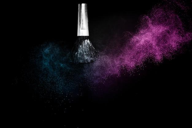 Cosmetische borstel met verspreiding van paarse en blauwe oceaankosmetische poeder Premium Foto