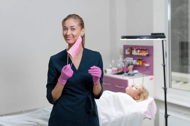 Cosmetische kabinet cliënt ligt op bank schoonheidsspecialiste staat roze beschermend medisch masker handschoen en glimlacht voorbereiding voor de procedure permanente wenkbrauw make-up volledige coronavirus bescherming covid-19 Premium Foto