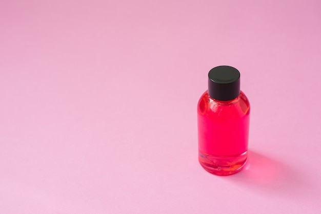 Cosmetische product fles roze met zwarte dop voor lichaamsverzorging cosmetica of haar op roze achtergrond. Premium Foto