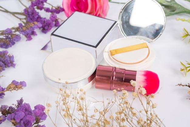 Cosmetische producten en bloemen op wit Gratis Foto