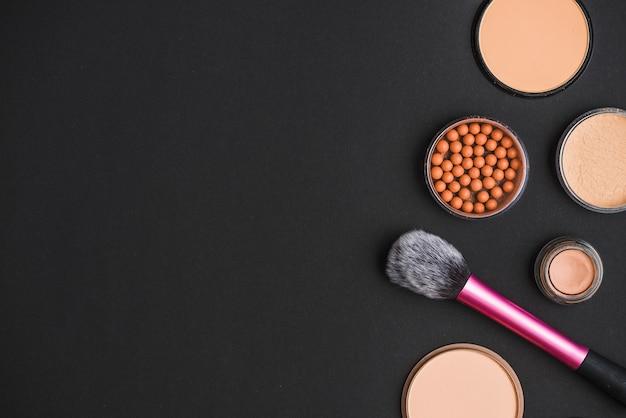 Cosmetische producten met make-upborstel op zwarte achtergrond Gratis Foto