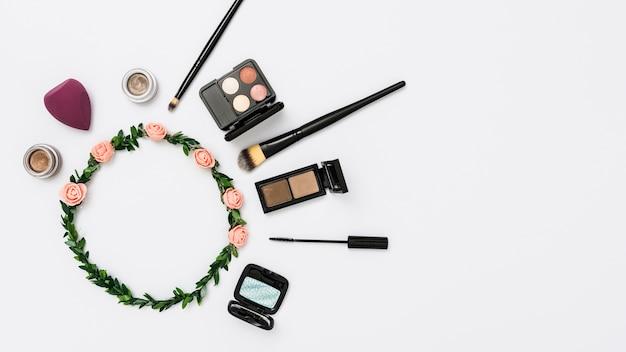 Cosmetische producten met roos en bladeren tiara geïsoleerd op een witte achtergrond Gratis Foto