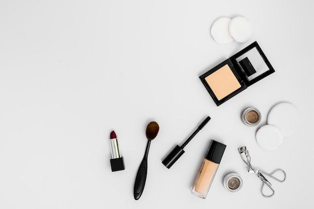 Cosmetische sponzen; compact poeder; fundament; lippenstift oogschaduw; wimper krultang en borstels op witte achtergrond Gratis Foto