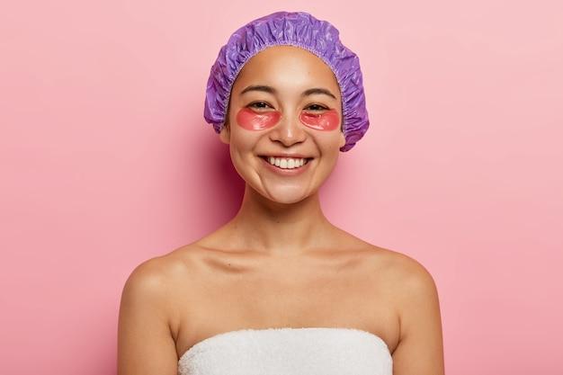 Cosmetologie en huidverzorging concept. vrolijke aziatische vrouw glimlacht positief, past hydrogelpleisters toe onder de ogen, draagt een douchemuts, staat shirtless, gewikkeld in een witte handdoek, geïsoleerd op roze muur Gratis Foto