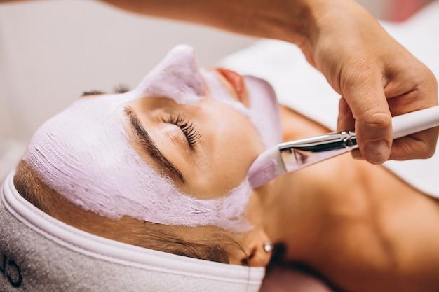 Cosmetologist die masker op een gezicht van cliënt toepast in een schoonheidssalon Gratis Foto