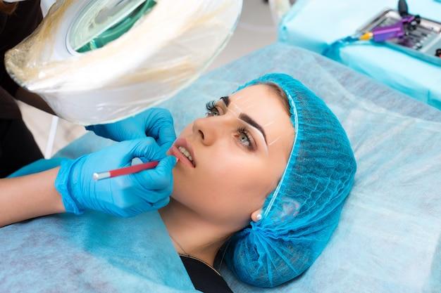 Cosmetologist die permanente make-up op vrouwengezicht maakt Premium Foto