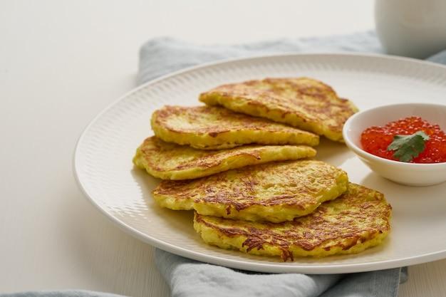 Courgettepannekoeken met aardappel en rode kaviaar Premium Foto