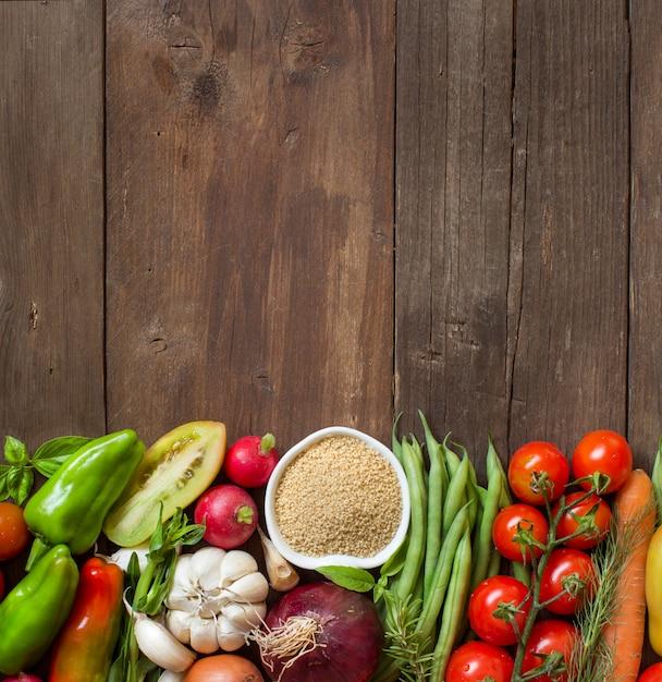 Couscous in een kom en verse groenten op de houten tafelblad-weergave met kopie ruimte Premium Foto