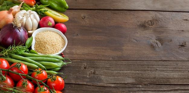 Couscous in een kom en verse groenten op een bruin houten tafel close-up Premium Foto