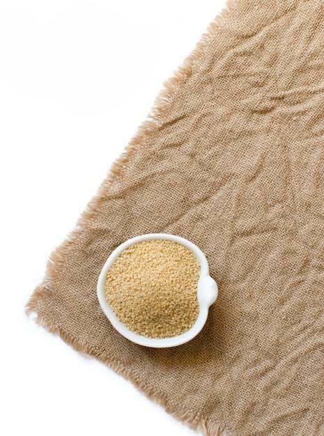 Couscous in een kom op jute bovenaanzicht geïsoleerd op wit Premium Foto
