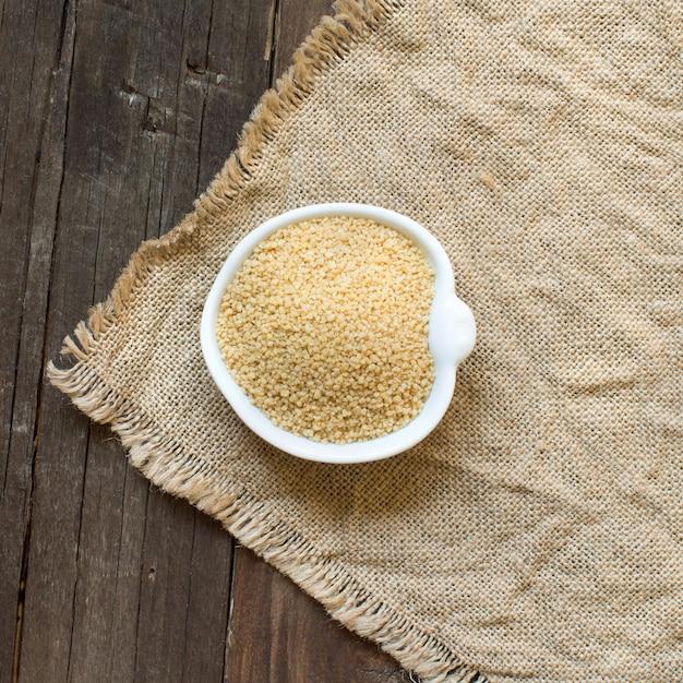 Couscous in een kom op jute bovenaanzicht op houten tafel Premium Foto